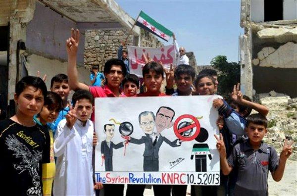Imagen de periodistas ciudadanos provista por la red noticiosa Edlib y acreditada con base en su contenido y otro reporteo de The Associated Press, en la que manifestantes que se oponen al gobierno sirio sostienen un póster que dibuja al presidente Bashar Assad (izquierda), al canciller ruso Sergei Lavrov (al centro) y al presidente de Estados Unidos Barack Obama (derecha), durante una protesta en Kafr Nabil, en el norte de Siria, el viernes 10 de mayo de 2013. (Foto AP/Red noticiosa Edlib)