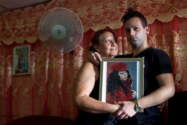 """Dayan Sánchez, 25, derecha, un gay un artista travesti conocido como """"Venus"""" posa con su madre Anadelia Morales, 47, en su casa en La Habana, Cuba. Una semana de desfiles, espectáculos y eventos culturales gays concluyó el viernes 18 de mayo de 2013. (AP Photo/Ramon Espinosa)"""