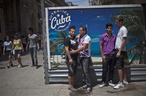 """Dayan Sánchez, 25, centro a la izquierda, un gay un artista travesti conocido como """"Venus"""" posa con Roberto García, 45, Gilberto Diez, 18, segundo de la derecha. Ernesto Nogues, 22, al frente de una valla turística en La Habana, Cuba, el jueves 16 de mayo de 2013. Una semana de desfiles, espectáculos y eventos culturales gays concluyó el viernes 18 de mayo de 2013. (AP Photo/Ramon Espinosa)"""
