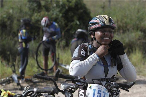 Mariane dos Santos se ajusta el casco el 20 de abril del 2013, lista para participar en la prueba anual Desafiando Límites para ciclistas ciegos por las calles de Brasilia. Con la ayuda de voluntarios videntes, los ciegos pueden disfrutar también de paseos en bicicletas e incluso de competencias. (AP Photo/Eraldo Peres).