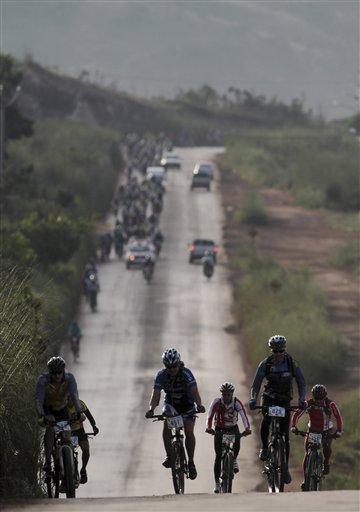 Ciclistas ciegos acompañados por voluntarios videntes participan en la carrera anual Desafiando Límited el 20 de abril del 2013 en las afueras de Brasilia.Con la ayuda de voluntarios, los ciegos pueden disfrutar también de paseos en bicicletas e incluso de competencias. (AP Photo/Eraldo Peres)