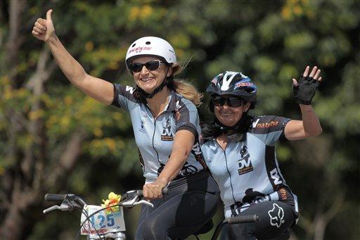 Ana Lidia Martins (der) y la voluntaria Anabe Lopes saludan durante un entrenamiento por las calles de Brasilia el 25 de abril del 2013. Con la ayuda de voluntarios, los ciegos pueden disfrutar también de paseos en bicicletas e incluso de competencias. (AP Photo/Eraldo Peres)