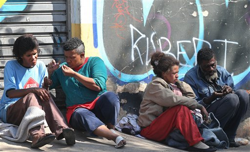 """Un hombre fuma cocaína crack en un barrio conocido como """"Crackland"""" en el centro de Sao Paulo. El estado más poblado y acaudalado de Brasil reveló el jueves 9 de mayo del 2013 un programa que pagará a las familias de adictos a la versión crack de la cocaína más de 600 dólares mensuales para pagar por su rehabilitación en centros de tratamiento privados. (AP Foto/Andre Penner)"""