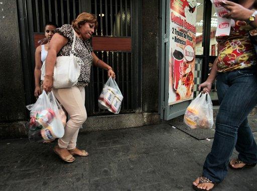 Una mujer sale de una tienda de Caracas con varias bolsas de productos, incluido papel higiénico, el miércoles 15 de mayo de 2014. Primero escasearon la leche, la mantequilla, el café y la harina de maíz. Ahora Venezuela se está quedando sin el más básico de los productos básicos: papel higiénico. Los economistas dicen que la escasez de diversos productos obedece por un lado a los controles de precios, con los que el gobierno busca que los productos básicos estén disponibles a los más pobres, y por el otro a los controles del gobierno a la moneda extranjera. (Foto AP/Fernando Llano)