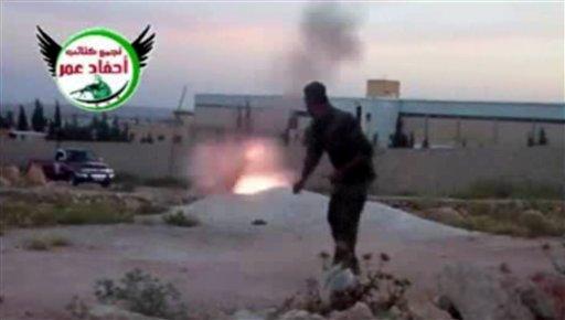 Esta imagen del video de un aficionado obtenida por un grupo que se autodenomina Ugarit News, consecuente con otros reportajes de la AP, muestra a un rebelde disparando un mortero en Alepo, Siria, el 28 de mayo del 2013 (AP Foto/Ugarit News via AP video)