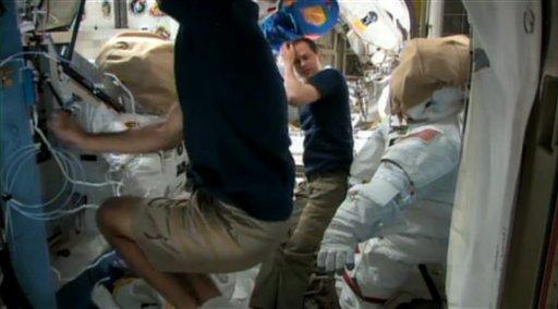 Los astronautas estadounidenses Chris Cassidy, al frente, y Tom Marshburn se preparan el viernes 10 de mayo de 2013 para una caminata espacial prevista para el sábado en la Estación Espacial Internacional. Intentarán reparar una fuga de amoniaco del mecanismo de refrigeración del sistema de electricidad de la estructura espacial. (AP Foto/NASA)