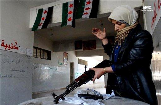 Esta imagen de periodismo ciudadano del martes 14 de mayo de 2013, proporcionada por el Aleppo Media Center AMC y cuya autenticidad ha sido verificada en base a su contenido y otra labor periodística de la AP, muestra a la madre de un insurgente sirio que limpia un fusil, en Alepo, Siria. (Foto AP/Aleppo Media Center AMC)
