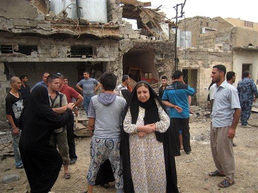 Residentes reaccionan luego de la explosión de un coche bomba en Kirkuk, 290 kilómetros al norte de Bagdad, Irak, el miércoles, 15 de mayo del 2013. Al menos 33 personas murieron en todo el país en ataques con bombas, dijeron las autoridades. (Foto AP/Emad Matti)