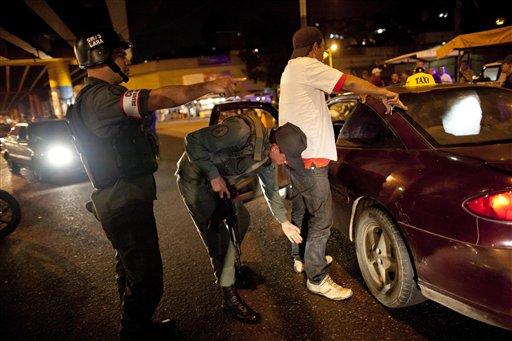 Soldados de la Guardia Nacional registran a un conductor de taxi en el barrio caraqueño de Petare el 14 de mayo del 2013. El gobierno sacó al ejército a las calles para tratar de contener la violencia, que hace que la tasa de asesinatos de Venezuela sea la quinta más alta del mundo. (AP Photo/Ariana Cubillos)