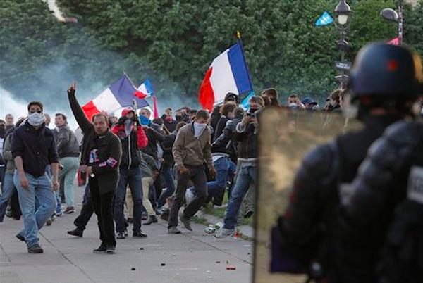 Policías antidisturbios (primer plano) enfrentan a manifestantes contra el matrimonio gay en París, Francia, el domingo 26 de mayo de 2013. Decenas de miles de personas protestaron en el centro de París contra la nueva ley que legaliza el matrimonio gay.(Foto AP/Laurent Cipriani)