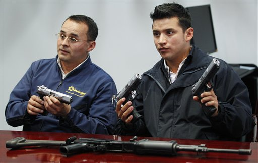 """En esta fotografía del 29 de abril de 2013, Javier Farigua, a la izquierda, y Edward López, sostienen prototipos de la nueva pistola """"Córdova"""" producida por la estatal Industria Militar en Soacha, Colombia. La pistola 9 milímetros saldrá al mercado en los primeros días de junio. (AP foto/Fernando Vergara)"""