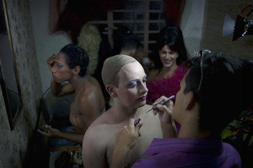 """En esta foto del 15 de mayo de 2013 photo, Gilberto Diez, derecha, aplica maquillaje a Dayan Sanchez, 25, un gay artista travesti conocido como """"Venus"""" preparándose para un espectáculo sobre moda en La Habana, Cuba. Una semana de desfiles, espectáculos y eventos culturales gays concluyó el viernes 18 de mayo de 2013. (AP Photo/Ramon Espinosa)"""