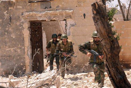 En esta fotografía divulgada el domingo 26 de mayo de 2013 por la agencia oficial de noticias de Siria, SANA, fuerzas sirias leales al presidente Bashar Assad corren para tomar su posición durante enfrentamientos con los rebeldes sirios en la ciudad de Alepo, Siria. (Foto de AP/SANA)