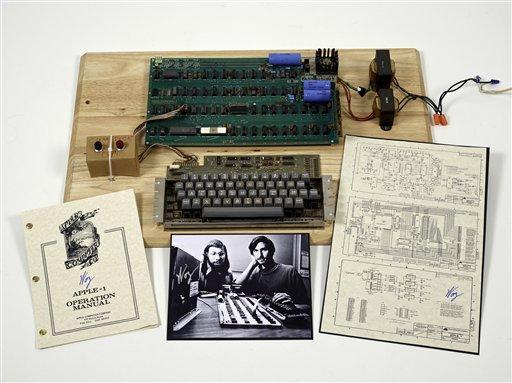 """Esta foto sin fechar suministrada por la casa de subastas Christie muestra un prototipo de computadora """"Apple 1"""", construida en 1976, junto con un manual de operación y esquemas, así como una foto de sus inventores: Steve Wozniak (izquierda) y Steve Jobs. Christies planea subastar una de las primeras Apple 1. (Foto AP/Christies Images Ltd. 2013)"""