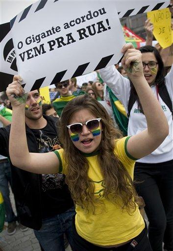 """Una manifestante sostiene un letrero que dice """"El gigante despertó. ¡Sal a las calles!"""" en una manifestación contra el gobierno brasileño en Porto, Portugal, el martes 18 de junio de 2013. (Foto AP/Paulo Duarte)"""