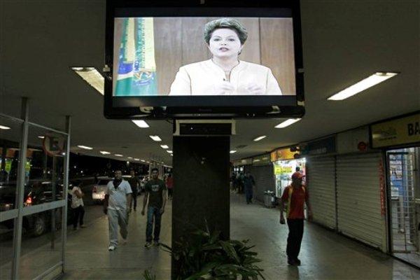 Un mensaje televisado de la presidenta de Brasil, Dilma Rousseff, se observa en una estación de autobuses en Brasilia, el viernes 21 de junio de 2013. La mandataria rompió el viernes su silencio casi absoluto después de más de una semana de multitudinarias y violentas protestas, al decir en un discurso transmitido por televisión en horario estelar que las protestas pacíficas son parte de una democracia sólida, pero que la violencia no puede ser tolerada. Prometió mejorar los servicios públicos, pero señaló que no se conseguirá de la noche a la mañana. (AP Foto/Eraldo Peres)