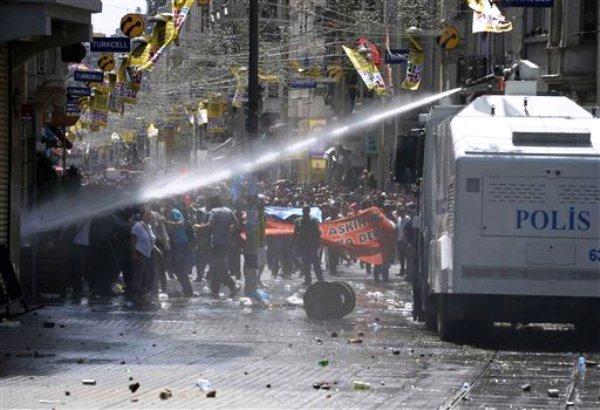 Policías antimotines se enfrentan el viernes 31 de mayo de 2013 con manifestantes luego de usar gas lacrimógeno y agua a presión en un operativo para dispersar una protesta pacífica realizada por cientos de personas para impedir la tala de árboles de un parque de Estambul. (Foto AP)