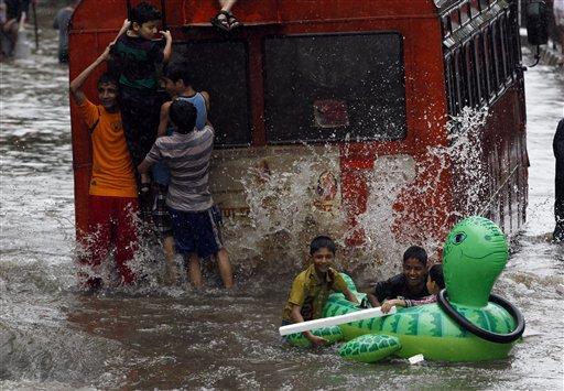 Niños juegan con un inflable en una calle inundada por las lluvias torrenciales en Mumbai, India, el domingo 16 de junio de 2013. Las inundaciones han dejado unas dos decenas de muertos, informó el gobierno el lunes. (Foto AP/Rajanish Kakade)