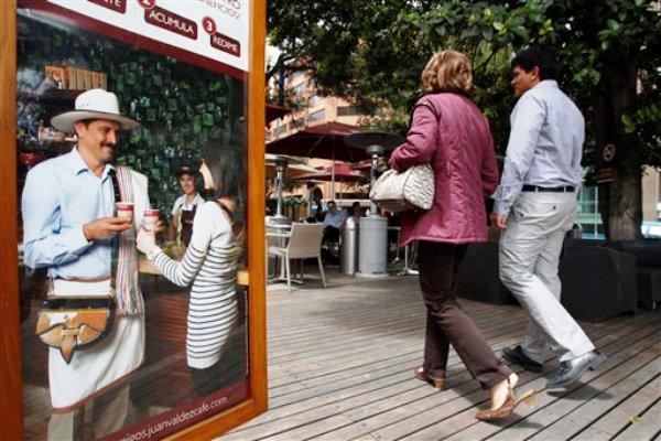 En esta foto del 7 de junio de 2013, una pareja ingresa a una cafetería Juan Valdez en Bogotá, Colombia. Juan Valdez, el personaje publicitario que ayudó a popularizar el café colombiano en el mundo, está siendo usado como modelo de gestión empresarial nada menos que en la prestigiosa universidad estadounidense. Por Liz Mineoy. (AP Photo/Fernando Vergara)