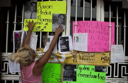 Una mujer coloca fotos en la entrada de un bar donde se produjo un secuestro masivo en la Ciudad de México, el 30 de mayo del 2013 (AP Foto/Eduardo Verdugo)