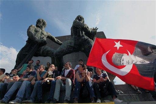 Manifestantes turcos con una banderola con la imagen del fundador del país, Kemal Ataturk, reunidos en la Plaza Kizilay en Ankara, la capital, el sábado 8 de junio de 2013. El primer ministro Recep Tayyip Erdogan se reunió el sábado con los líderes de su partido en momentos que las protestas contra el gobierno entran en su noveno día y miles de personas siguen ocupando la central Plaza Taksim en Estambul. (Foto AP/Burhan Ozbilici)