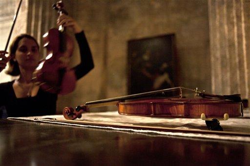 Una violinista prepara su instrumento para un concierto en el ex Convento de San Francisco de Asis en La Habana, Cuba, el jueves 20 de junio de 2013. En el concierto en el ex convento convertido en centro cultural se presentaron piezas que no se escuchaban desde el siglo XVIII. (Foto AP/Ramon Espinosa)