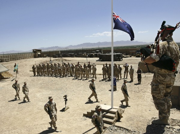 Australian and British troops stand at attention during an ANZAC day ceremony at Camp Armadillo in Helmand Province