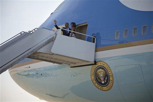 El presidente de Estados Unidos Barack Obama y su esposa Michelle saludan antes de abordar el avión presidencial en la Base Andrews de la Fuerza Aérea, en Maryland, el miércoles 26 de junio de 2013, antes de viajar a Senegal, Sudáfrica, y Tanzania. (Foto AP/Evan Vucci)
