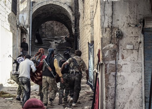 Un grupo de rebeldes del Ejército Sirio Libre cargan a un camarada herido en el pueblo de Harem, Siria, (Foto AP/Mustafa Karali, Archivo)