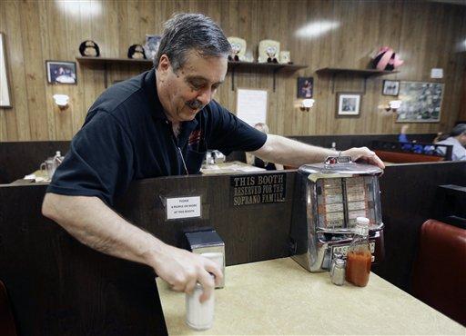 """Chris Carley, propietario de la fuente de sodas Holsten, donde se filmó el ultimo programa de la serie de HBO""""Los Soprano"""" mueve una rocola para mostrar un letreoro que dice """"mesa reservada para la familia Soprano"""", el miércoles 19 de junio de 2013, en Bloomfield, Nueva Jersey. Gandolfini fue recordado en las ciudades de Nueva Jersey donde se grabó el programa (Foto AP/Julio Cortez)"""
