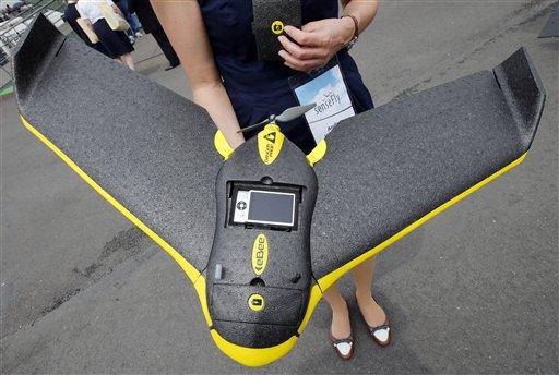 Personal de la empresa Sensefly muestran un avión teledirigdo ultraligero eBee de uso civil profesional y que permite tomar fotografías y video, durante la edición 50 de la Exhibición Aérea de París en el aeropuerto de Le Bourget, al norte de París, el martes 18 de junio de 2013. (Foto AP/Francois Mori)