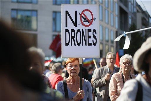 Una manifestante sostiene un cartel contra el uso militar de aviones no tripulados durante una protesta previo a la visita del presidente estadounidense Barack Obama a Berlín en una gira de dos días a la capital alemana, el lunes 17 de junio de 2013. (Foto AP/Markus Schreiber)
