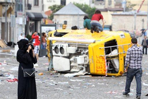 En esta fotografía del domingo 2 de junio de 2013, una turista toma fotos del daño en la plaza Taksim de Estambul. Turquía vive la ola más grande de protestas contra el gobierno de los últimos años. (Foto AP/Thanassis Stavrakis)