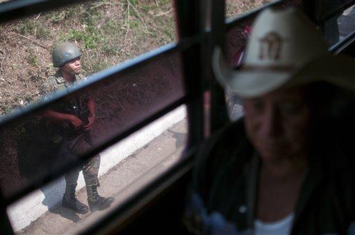 Fotografía de archivo del 2 de mayo de 2013 de un soldado observando un autobús en un retén en Mataquescuintla, Guatemala. El gobierno declaró estado de sitio y prohibió las concentraciones públicas y otras libertades civiles en cuatro pueblos próximos a la mina de plata de San Rafael, inclusive Mataquescuintla, tras choques violentos entre policías y residentes que protestaron contra el proyecto minero El Escobal, manejado por extranjeros. Una queja común es que los vecinos sienten que no se les consultó sobre el proyecto antes de su aprobación. (Foto AP/Luis Soto)