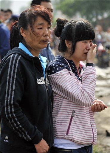 Familiares de un trabajador en una foto tomada del 3 de junio del 2013 por la agencia de noticias oficial Xinhua mientras esperan información después de un incendio ocurrido en una granja avícola de propiedad de Jilin Baoyuanfeng Poultry Company en Mishazi Township de Dehui City, en la provincia de Jilin en el noreste de China. Un enorme incendio en una granja avícola en China destruyó el lugar por completo, y causó la muerte a 119 trabajadores que quedaron atrapados en los cobertizos. (Foto AP/Xinhua, Wang Haofei)