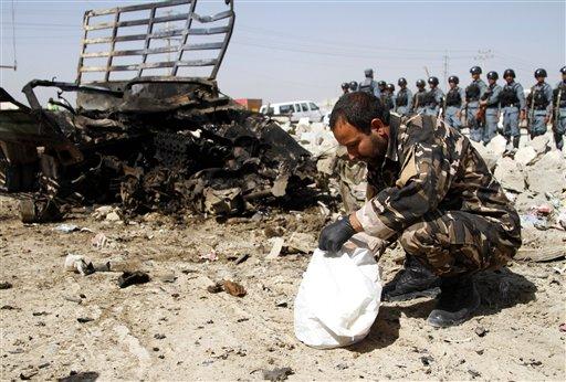 Un oficial de seguridad e inteligencia afgana inspecciona el lugar de un atentado suicida cerca del aeropuerto militar de Kabul en Afganistán el lunes 10 de junio de 2013. (Foto AP/Ahmad Jamshid)