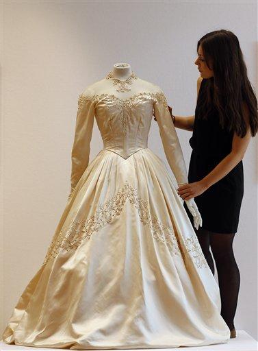 Una empleada de la casa de subastas Christie's ajusta el primer vestido de novia de Elizabeth Taylor diseñado por la vestuarista Helen Rose en Christie's en Londres el miércoles 19 de junio de 2013. El vestido es parte de una subasta de 120 años de cultura pop que incluye objetos del siglo pasado de figuras de la música y el cine. Se espera que el vestid se venda entre 30.000 a 50.000 libras esterlinas (47.000 a 78.000 dólares). (Foto AP/Frank Augstein)
