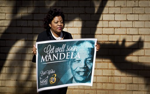 Una mujer con  un cartel que le desea mejoría al ex presidente Nelson Mandela llega al Hospital Mediclinic Heart en Petroria, la capital sudafricana, donde recibe tratamiento el otrora  líder contra el apartheid en Sudáfrica el domingo 16 de junio del 2013. (Foto AP/Ben Curtis)
