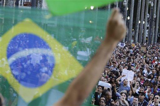 Un manifestante sostiene la bandera brasileña frente a una multitud congregada en la principal plaza de Sao Paulo, Brasil, el martes 18 de junio de 2013. (Foto AP/Nelson Antoine)