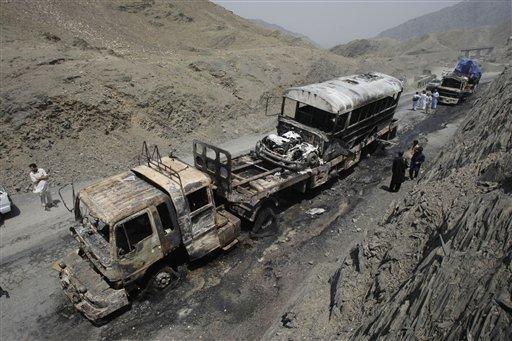 Personal de seguridad de Pakistán y pobladores de aldeas vecinas observan los camiones de un convoy de la OTAN destrudos en un ataque de milicianos disfrazados de policías en la región de Khyber el lunes 10 de junio del 2013. Un funcionario paquistaní dijo que ataques con cohetes destruyeton camiones de suministro de la OTAN y causaron la muerte a varias personas. (Foto AP/Mohammad Sajjad)