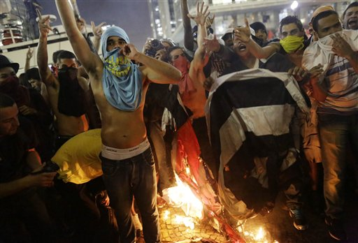 Manifestantes queman una bandera del estado de Sao Paulo frente al ayuntamiento, en Sao Paulo, Brasil, el martes 18 de junio de 2013. Algunas de las mayores protestas desde el final de la dictadura brasileña (1964-85) han estallado a lo largo y ancho de este país de dimensiones continentales, convocando a multitudes frustradas por servicios deficientes a pesar de los altos impuestos. (AP Foto/Nelson Antoine)