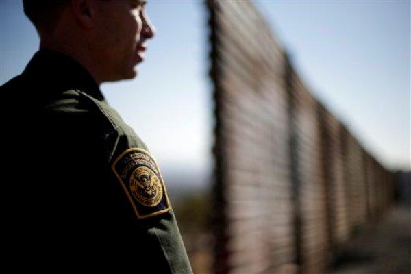 La foto del 13 de junio de 2013 muestra al agente la patrilla fronteriza Jerry Conlin viendo hacia el norte, cerca del muro  que separa Tijuana en México de la ciudad de San Diego en Estados Unidos. El Senado y la Cámara de Representantes de Estados Unidos debaten proyectos de reforma migratoria separados. (AP foto/Gregory Bull)