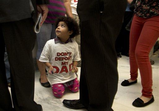 """Jackelin Alfaro, de 4 años, vestida con una camiseta que dice en inglés """"No deporten a mi papá"""", se sienta en el piso acompañada por sus familiares afuera de una audiencia del Comité de Asuntos Jurídicos de la Cámara de Representantes de Estados Unidos el martes 18 de junio de 2013, donde se votaría una medida para permitir a autoridades locales aplicar leyes migratorias. (Foto AP/Carolyn Kaster)"""