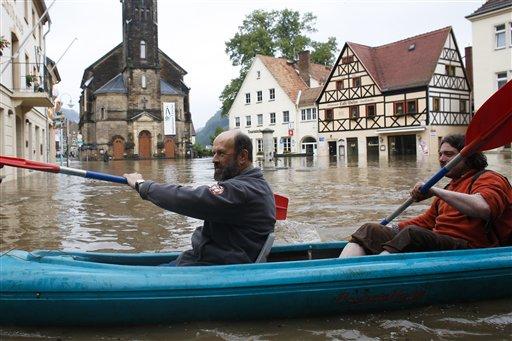 Dos hombres reman por una zona comercial inundada por el río Elba, el martes 4 de junio de 2013 en Wehlen, Alemania. (Foto AP/Markus Schreiber)