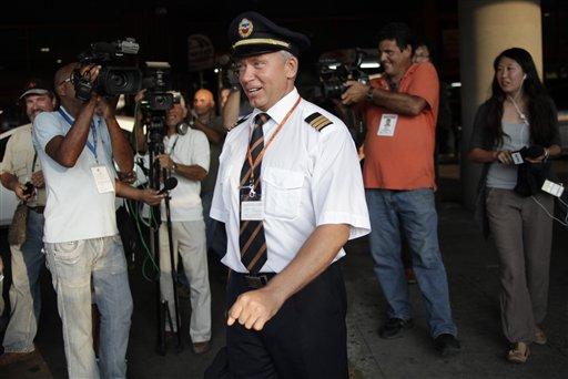 Periodistas rodean a un miembro de la tripulación del vuelo de Aeroflot SU150 en el que presuntamente viajaba Edward Snowden y procedente de Moscú, en el aeropuerto internacional de La Habana, Cuba, el lunes 24 de junio de 2013. (Foto AP/Ramon Espinosa)