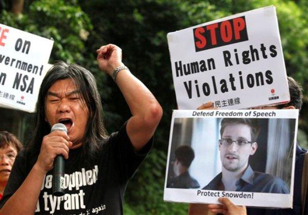 Varios manifestantes empuñan fotos de Edward Snowden, un ex empleado de la CIA que filtró información secreta sobre el espionaje estadounidense, frente al consulado de Estados Unidos en Hong Kong el jueves, 13 de junio del 2013. (Foto AP/Kin Cheung)