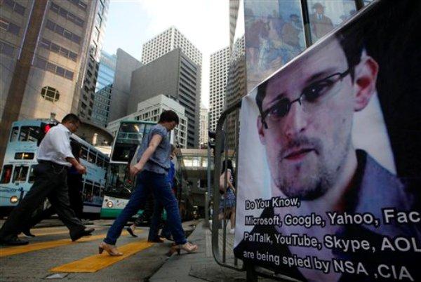 Los peatones pasan frente a un cartelón con la imagen de Edsard Snowden, que reveló planes secretos de espionaje en Estados Unidos, por el distrito comercial de Hong Kong el 17 de junio del 2013 (AP Foto/Kin Cheung)