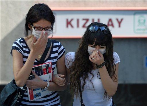 Dos turcas sufren los efectos de los gases lacrimógenos en la Plaza Kizilay, cerca de la oficina del primer ministro Recep Tayyip Erdogan, en Ankara el martes, 4 de junio del 2013. Las protestas contra el dirigente islámico han aumentado en todo el país, especialmente en Estambul. (Foto AP/Burhan Ozbilici)