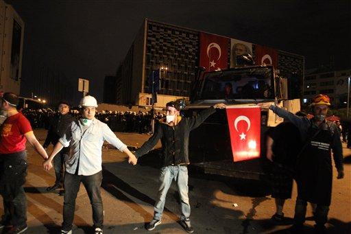 Manifestantes forman una cadena humana frente a elementos de la policía en plaza Taksim de Estambul la noche del miércoles 12 de junio de 2013. (Foto AP/Thanassis Stavrakis)