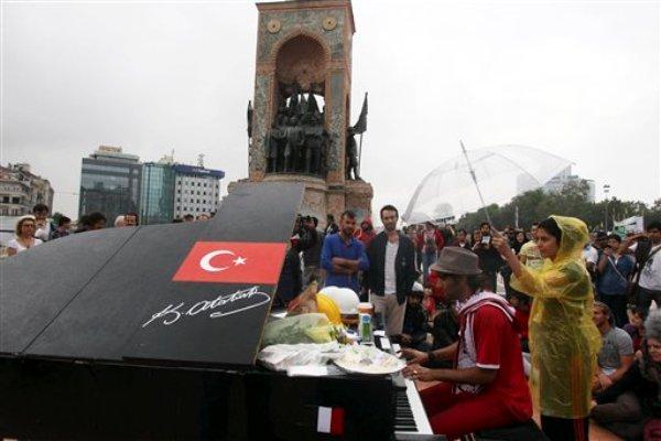 Una persona toca el piano mientras un manifestante lo cubre con un paraguas al pie del monumento a Mustafá Kemal Ataturk, fundador de la Turquía moderna, en la plaza Taksim de Estambul el viernes 14 de junio de 2013. (Foto AP/Thanassis Stavrakis)